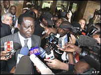 Raila Odinga (C) is mobbed by media as leaves a Nairobi hotel this month