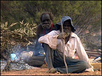 Two Aboriginal men sit by a fire (file image)