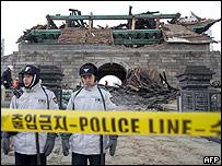 Dos policías resguardan los restos de la puerta de Namdaemun