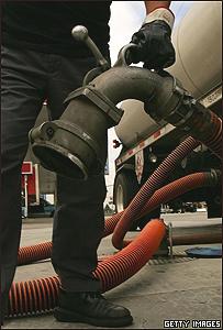 Un hombre sostiene una manguera de gasolina