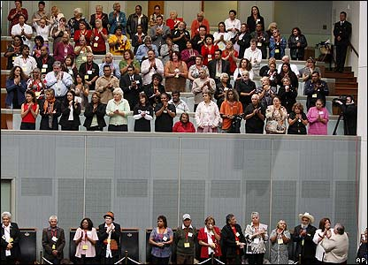 "Members of the public and Australia's ""Stolen Generation"" applaud in the public gallery in parliament"