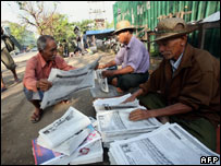 Men sell newspapers containing the announcement in Rangoon on 10 February 2008