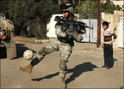 An Iraqi boy watches a US soldier kick a football in Baghdad, Iraq (13/02/2008)