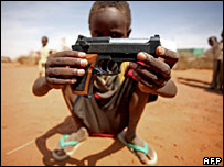 Boy in Darfur with a replica gun saying 'Made in China'