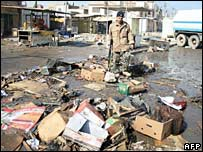 Iraqi soldier surveys the debris in Baghdad's Jadida market after a bombing on 1 February 2008