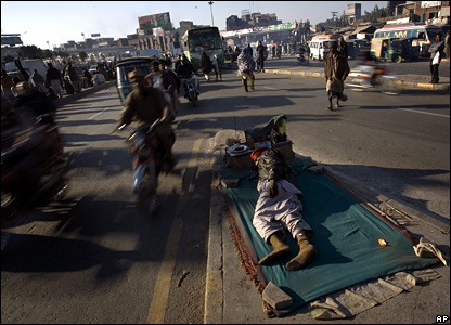 A man sleeps on a traffic island in the middle of a road in Lahore