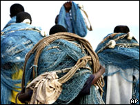 Fishermen carry their nets in Ghana