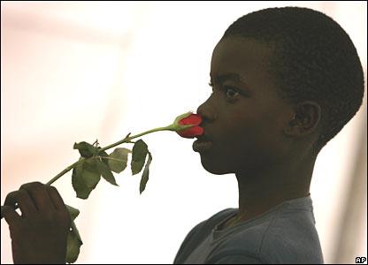 Kenyan refugee boy smells a rose