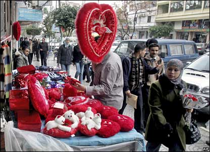 Palestinians walk past a shop selling Valentine's Day gifts in Gaza City