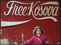 A girl runs past graffiti reading Free Kosovo in the town of Mitrovica, Kosovo