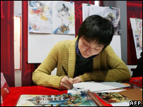 A Japanese artists signs books at the comics fair