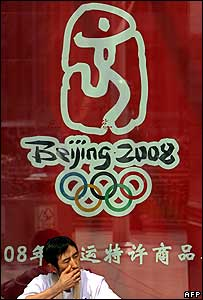 Man smoking underneath Beijing Olympic logo