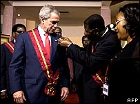 Benin President Thomas Yayi Boni presents US President George W. Bush with the Grand Cross of the National Order of Benin