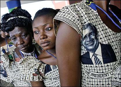 Women in Tanzania wait at airport wearing dresses with President Bush images printed on them.