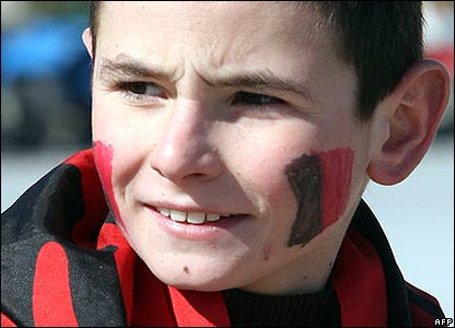 Boy with red and black paint on his cheeks, Tirana, Albania