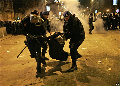 Police officers carry an injured colleague during clashes with protesters outside the US Embassy in Belgrade, Serbia