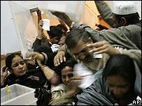 Trabajadores electorales forcejean para recoger urnas para sus distritos en Lahore