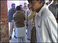Men waiting outside the Khazana polling station where Shaheen is officiating