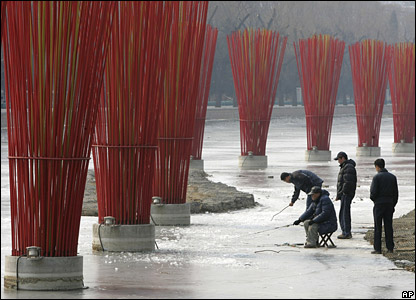 Chinese men fish through holes in the ice on a frozen canal in the capital, Beijing.