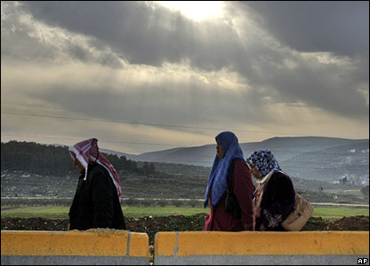 Palestinians walk through the Hawara checkpoint