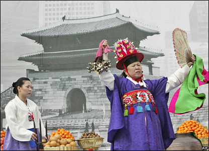 A South Korean shaman, Han Soon-ye, performs a mourning ceremony for the Namdaemun Gate in front of a photo of the monument