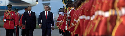 US President George W. Bush (C) and Tanzanian President Jakaya Mrisho Kikwete review the troops during an arrival ceremony at Julius Nyerer International Airport in Dar se Salaam