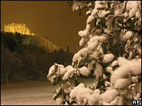 A tree covered with snow and Athens' Acropolis in the background