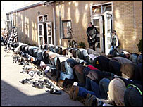 Muslims kneeling outside