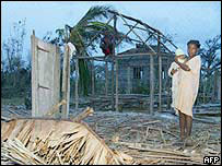 Villagers stand by ruined homes in Ambomalasa after a cyclone in 2004