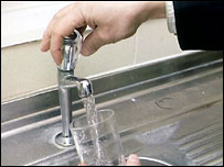 Person filling up a glass with tap water