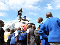 Schoolchildren wait to board a bus to school in Harare