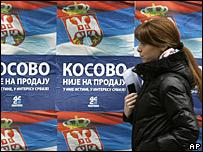 """Una mujer camina frente a unos carteles que dicen """"Kosovo no está en venta"""",  en Serbia"""