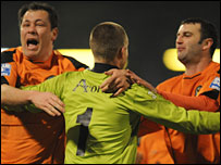 Keeper Glyn Thompson is mobbed after Newport's penalty shoot-out win