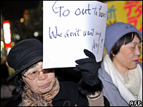 A woman holds a sign at a protest outside the US embassy in Tokyo on 13 February 2008