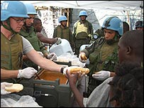 Food writer Stefan Gates helping to handing out food in Cite Soleil, Haiti
