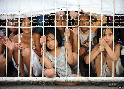 Philippine children try to get a view of President Gloria Arroyo