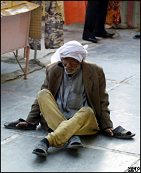 An paralysed beggar sits outside shops in Baghdad's al-Shaab neighbourhood (29 January 2008)
