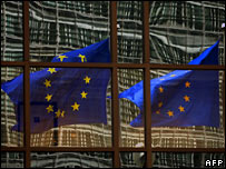 EU flags reflect in a building of the EU headquarters in Brussels