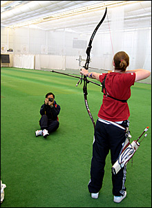 Naomi Folkard shoots an arrow while being photographed from various angles