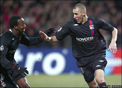 Lyon's Sidney Govou congratulates goalscorer Karim Benzema
