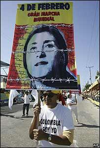 Hombre levanta un cartel con la foto de Ingrid Betancourt durante una marcha