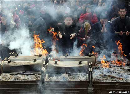 People pray in front of incense burning in Changchun, 21 February 2008