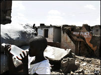 Child drinks water in front of burnt houses in Kibera slum, Nairobi, Kenya (16.02.08)