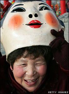 A performer lifts a mask in Changchun, Jilin Province, February 21 2008