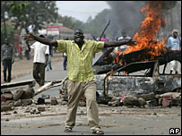 A man walks away from a burning car after riots in Kisumu in Kenya (AP Photo: Darko Bandic)