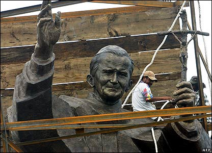 East Timorese workers make a finishing touch to a statue of Pope John Paul II in Dili