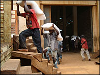 Men carrying sacks on their heads from the World Food Programme warehouse in Kampala