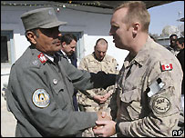 An Afghan police officer greets a Canadian soldier in Kandahar - 8 February 2008