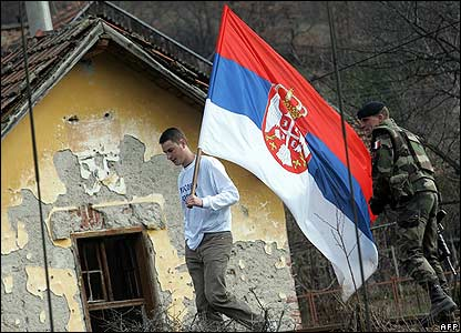 A Kosovo Serb with a Serbian flag passes by French peacekeeper at Jarinje border crossing in Kosovo