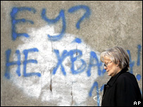 "A woman walks past graffiti in Belgrade saying ""EU? No thanks!"""